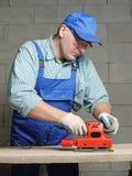 Sanding work. Carpenter in jumpsuit sanding plank using power finishing sander Stock Images