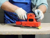 Sanding work. Closeup of carpenters hands sanding plank using power finishing sander Stock Photography