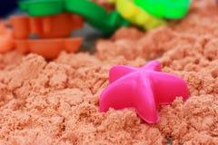 Sandlådabarns är konstgjord sand för lekplats där många leksaker royaltyfri bild