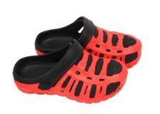 Sandálias de borracha da criança vermelha isoladas no fundo branco Fotos de Stock