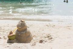 Sandman z kokosowym napojem na plaży Obrazy Royalty Free