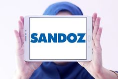 Sandoz pharmaceutical company logo. Logo of Sandoz company on samsung tablet holded by arab muslim woman. Sandoz is a global leader in generic and biosimilar Stock Images