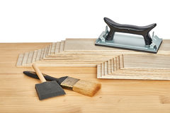 Sandpaper holder, stack of veneers and paint brushes Royalty Free Stock Images