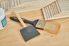 Sandpaper holder, stack of veneers and paint brushes Stock Photography