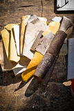 Sandpapers of different colors on old wood carpentry. Royalty Free Stock Image