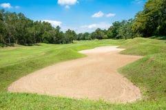 Sandpappra grönt gräs för bunker och blå himmel i golfklubb arkivbilder
