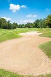 Sandpappra grönt gräs för bunker och blå himmel i golfklubb Royaltyfria Bilder