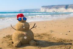 Sandpappra jultomtensnögubben med hatten på stranden Royaltyfri Fotografi