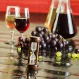 Sandpappra klockan, druvor, vinflaskor och vinexponeringsglas royaltyfria bilder