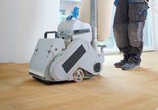Sandpappra parketten med den malande maskinen Polering reparation in Arkivfoton