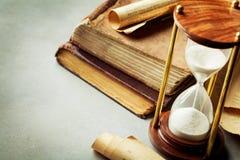 Sandpappra spring till och med timglaset och de gamla tappningböckerna Tid vårdarebegrepp arkivfoto