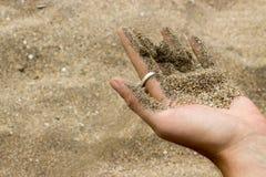 Sandpappra spring ut från handen på stranden arkivbild