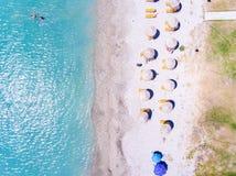 Sandpappra stranden i Grekland den flyg- sikten med paraplyer och solstolar fotografering för bildbyråer