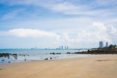 Sandpappra stranden och revstranden i havsikt med cityscape Royaltyfri Bild