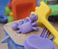 Sandpit. A bucket with sand, a crab shaped sand mould, a sieve and a yellow fork, with other toys in the background Stock Image