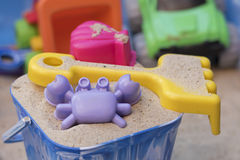 Sandpit. A bucket with sand, a crab shaped sand mould and a yellow fork, with other toys in the background Royalty Free Stock Image