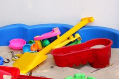 Sandpit with colorful toys. Colorful toys lie piled together in sandpit Stock Image