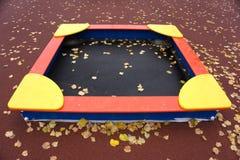 Sandpit, en un fondo rojo con las hojas caidas Fotos de archivo libres de regalías