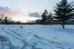 Winter Sunrise at Golf Course. A sandpit at a golf course covered in snow, and the sun setting in the distance. It is now called Acacia metropark Royalty Free Stock Photography