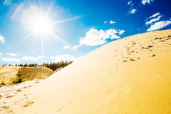 Sandpit lit by the bright midday sun on blue sky. Background Royalty Free Stock Photos