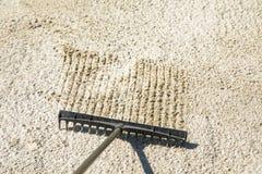 Sandrührstange in einer Golffalle, den Sand harkend Lizenzfreies Stockbild