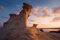 Sandrockcijfer in het licht van zonsopgang op een rotsachtig strand Noordelijk Cyprus stock afbeeldingen
