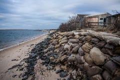 Sandsäckar på stranden som omger huset royaltyfri foto