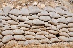 Sandsäckar som travas upp som skydd för mindre jordras royaltyfri bild