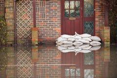 Sandsäckar utanför Front Door Of Flooded House Fotografering för Bildbyråer