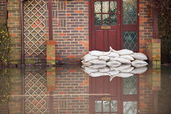 Sandsäcke außerhalb Front Door Of Flooded Houses Stockbild