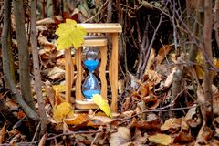 Sands clock in the autumn forest among trees and dry leaves. Autumn time. Autumn came_. Sands clock in the autumn forest among trees and dry leaves. Autumn time stock photography