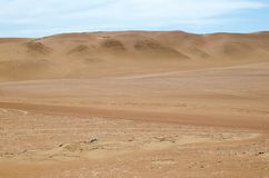 Sands of the desert under bright blue sky with few clouds stock images