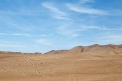 Sands of the desert under bright blue sky with few clouds stock photo