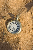 The sands of time. An image of a silver pocket watch on a sandy shore. A concept image of the sands of time Stock Photography