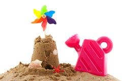 Sandschloß und -spielwaren am Strand Stockfotografie