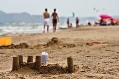 Sandschloß und -touristen auf spanischem Strand Lizenzfreies Stockfoto