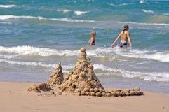 Sandschloß und zwei junge Mädchen Lizenzfreie Stockfotos