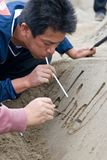 A sandsculpture artist at work. Kagoshima, Japan, April 30, 2007, A sandsculpture artist using a straw to blow loose sand from letters carved into a sand royalty free stock photo
