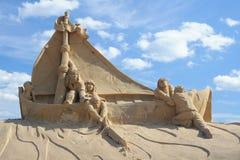 Sandskulptur: besparingfolket seglar in fartyget Royaltyfria Bilder