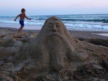 Sandskulptur och pojke Arkivbild