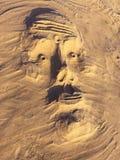 Sandskulpturmaskering på en strand Arkivfoto