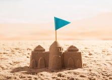 Sandslott med flaggan på havskusten Arkivfoto