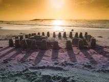 Sandslott på stranden i strålarna av solnedgången Arkivbild
