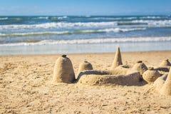 Sandslott på stranden med rullande vågor i bakgrund Royaltyfri Foto