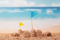 Sandslottar och torn med flaggor på bakgrund av havet Arkivbild