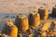 Sandslottar på solnedgången arkivfoton