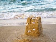 Sandslotten återstår med snäckskal, havet i bakgrunden arkivfoton