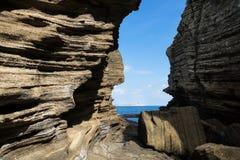 Sandsteinklippen mit Abstand mit Ansicht zum Ozean bei Yongmeori setzen, Sanbang-ro, Jeju-Insel, Südkorea auf den Strand Lizenzfreies Stockbild