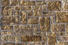 Sandstenvägg, bricked med den olika storleksanpassade vässade lantliga stenen och vita skarvar royaltyfri foto