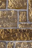 Sandstenvägg, bricked med den olika storleksanpassade vässade lantliga stenen och vita skarvar arkivbild